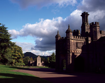 Ilam Hall entrance portico with Thorpe Cloud in dark shadow behind the parish church