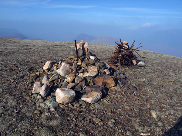 Old ridge fence entangled into the summit cairn